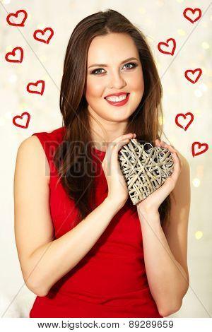 Smiling girl holding wicker heart on festive background