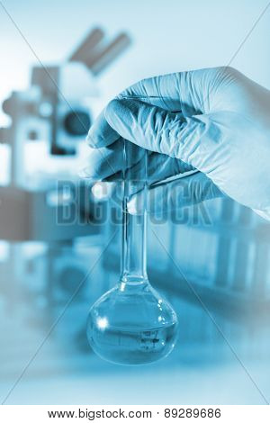 Flask in scientist hand in laboratory