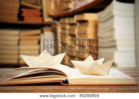 Open book with paper boats on bookshelves background