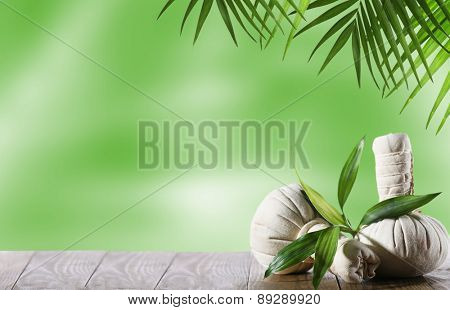 Spa compress balls with leaves on green background