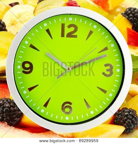Food clock with fruits as background. Healthy food concept