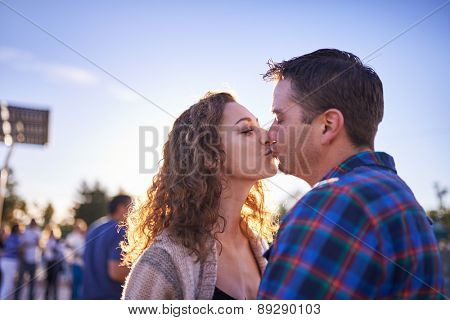 couple kissing in crowd at sunset