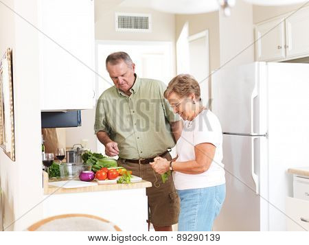 elderly husband and wife making dinner together in kitchen shot with selective focus