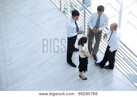 Businessmen and woman standing together by railing and conversing