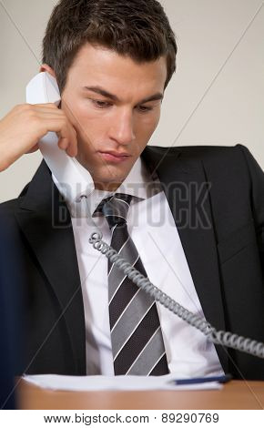 Businessman conversing on landline phone