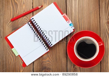 Office table with blank notepad and red coffee cup. View from above with copy space