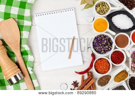 Various spices on white wooden background. Top view with notepad for copy space