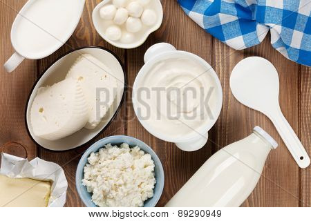 Dairy products on wooden table. Sour cream, milk, cheese, yogurt and butter. Top view
