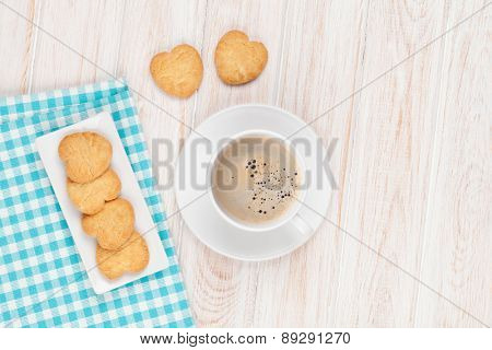 Coffee and heart shaped cookies on white wooden table with copy space