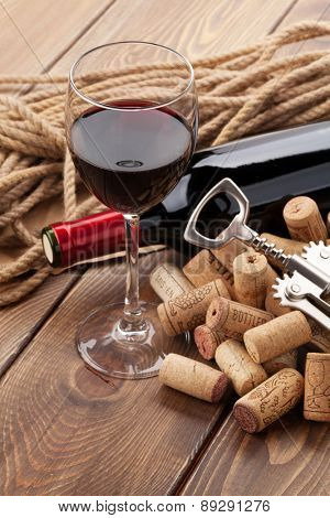 Glass of red wine, bottle and corkscrew on rustic wooden table