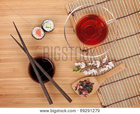 Sushi maki set, herbal tea and sakura branch over bamboo table