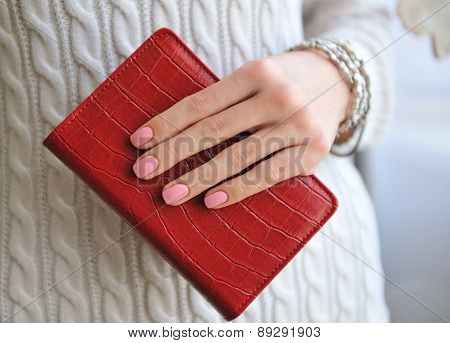 Red notebook in a female hand