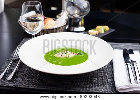 Broccoli cream soup with white fish and scallops