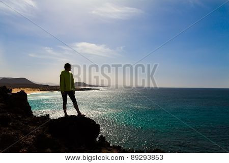 Silhouette of hiking woman near sea