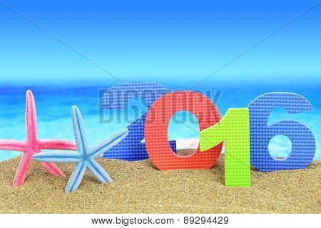 New year number 2016 and starfishes on the beach