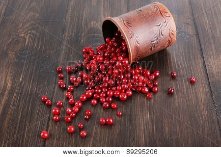 Red cranberries with clay cup on wooden background