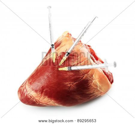 Raw animal heart and syringes isolated on white