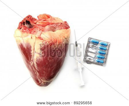 Raw animal heart with syringe and tablets isolated on white