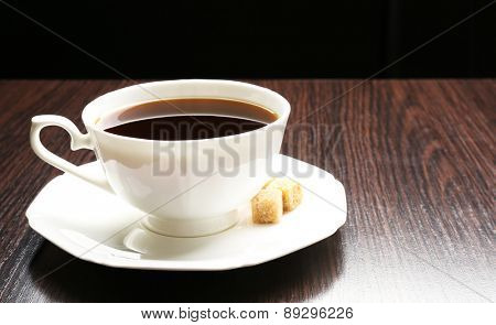 Cup of coffee with lump sugar on wooden table, on dark background