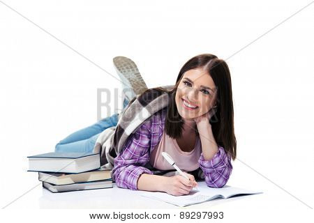 Cheerful woman lying on the floor and writing in notebook over white background and looking at camera