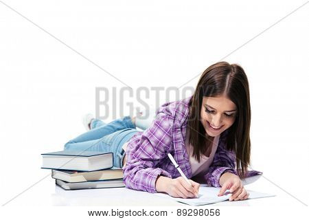 Smiling woman lying on the floor and writing in notebook over white background