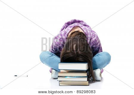 Tired woman sitting on the floor and sleepiing on books over white background