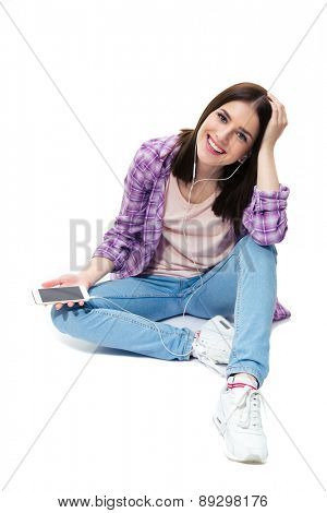 Smiling young girl sitting on the floor with smartphone over white background and looking at camera