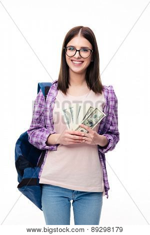 Young femael student with backpack holding money over white background and looking at camera