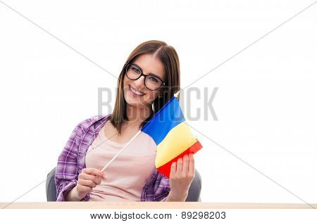 Young woman sitting at the table with french flag over white background