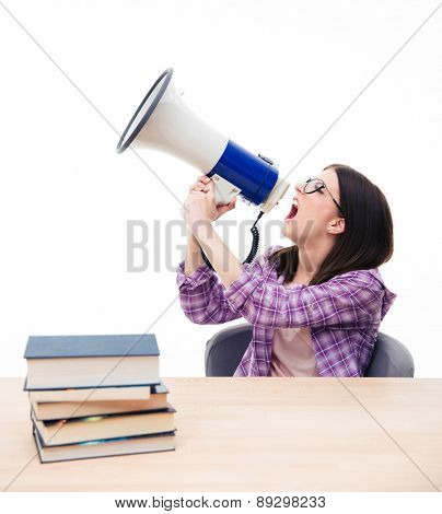 Young female student sitting at the table with books and shouting in megaphone