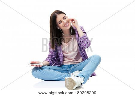 Happy woman sitting on the floor and listening music in headphones over white background