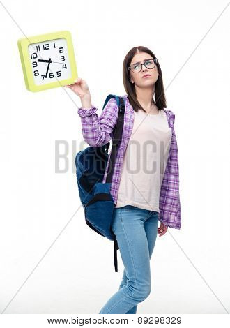 Sad female student with backpack looking at big clock over white background