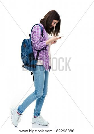 Full length portrait of a happy young female student using smartphone over white background