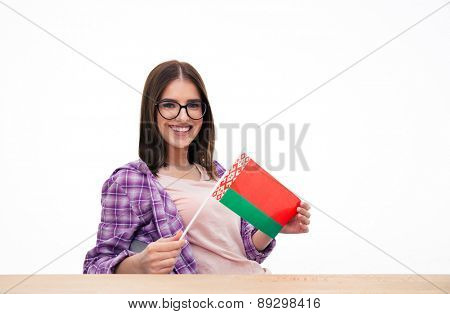 Smiling woman sitting at the table with Belarussian flag over white background and looking at camera