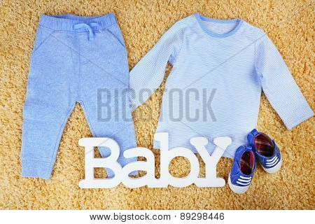 Clothes for baby boy on colorful background