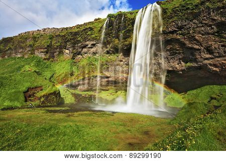 Large rainbow decorates a drop of water. Seljalandsfoss waterfall in Iceland. Summer sunny day