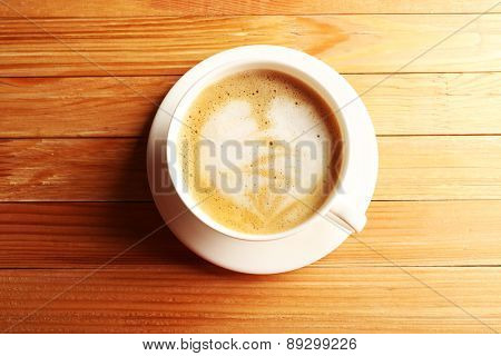 Cup of coffee latte art on wooden table, top view