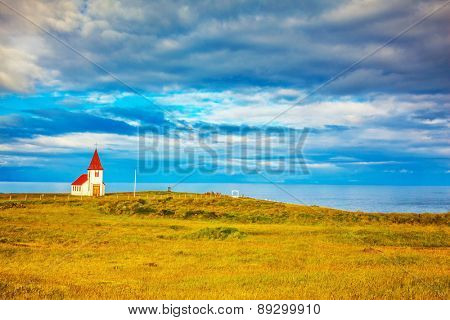 Iceland. White Chapel with red roof on the northern fjord