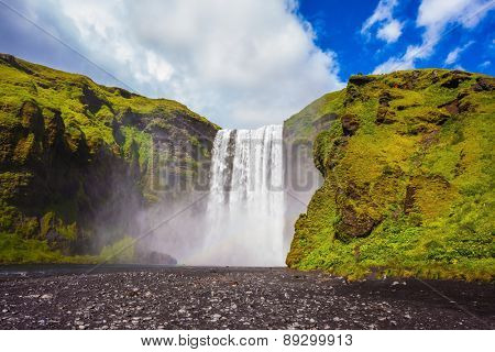 Iceland, waterfall Skogafoss summer, clouds of mist. Huge waterfall flowing from under giant glacier