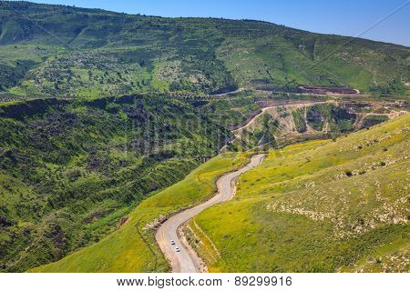 Serpentine road winds through the green hills. Israel's border with Jordan about the hot springs of Hamat Gader