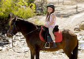 image of horse girl  - sweet beautiful young girl 7 or 8 years old riding pony horse and smiling happy wearing safety jockey helmet posing outdoors on countryside in summer holiday - JPG