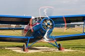 stock photo of propeller plane  - Old bright blue airplane with a rotating propeller close - JPG