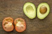 stock photo of avocado  - avocado and tomato cut in half on a grunge wood with a copy space - JPG
