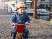 image of tricycle  - Cute toddler riding his tricycle in Amsterdam - JPG