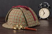 foto of private investigator  - Deerstalker Hat and magnifying glass on Old Wooden table - JPG