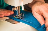 pic of stitches  - Soft blue fabric getting sewn up with a zigzag stitch. ** Note: Shallow depth of field - JPG