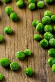 image of sweet pea  - Organic frozen baby sweet peas on wood board - JPG