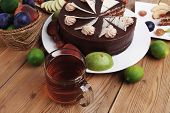 picture of cream cake  - chocolate cream brownie cake layers slice topped with white chocolate and cream flowers decorated with fruits apple plum and grape on plate on wooden table with big whole cake - JPG