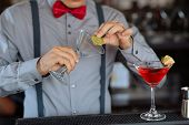 picture of bartender  - Hands of bartender running a slice of lime around the rim of the glass to make Margarita - JPG