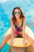 image of mattress  - Young pretty woman with perfect tanned body lying on yellow air mattress in the pool in summer and having fun - JPG